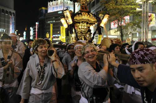 các du khách hào hứng tham gia nâng mikoshi